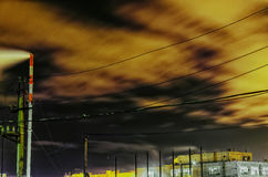 Paysage industriel de nuit avec des vues de l'usine de tuyau dans la distance Puisque le tuyau est fumée et des nuages dans le ci Image libre de droits