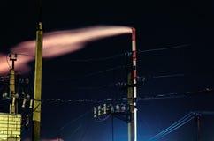 Paysage industriel de nuit avec des vues de l'usine de tuyau La fumée sort du tube rouge et blanc Images stock