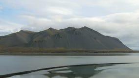Paysage islandais calme et dramatique avec les montagnes foncées et la rivière large par temps nuageux clips vidéos