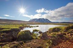 Paysage islandais de nature d'été avec le soleil, le lac et la montagne Photographie stock
