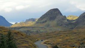 Paysage islandais unique avec le gisement de lave, les collines, la route d'enroulement et la voiture mobile, dans le jour d'auto banque de vidéos