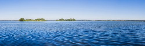 Paysage, jour lumineux Arbres, l'eau, ciel lumineux Image stock