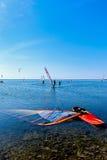 Paysage marin avec des surfers et des planches à voile Photos stock