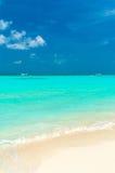 Paysage marin avec des vagues de roulement sur une plage sablonneuse et des bateaux, Maldives photos libres de droits