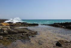 Paysage marin avec des vagues se brisant contre des roches Images stock
