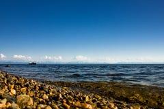 Paysage marin avec la plage en pierre près du lac avec des montagnes à l'arrière-plan Images libres de droits