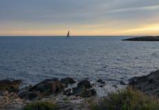 Paysage marin avec le voilier au-dessus du coucher du soleil photos stock