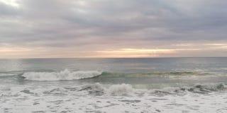 Paysage marin de coucher du soleil Le soleil traverse les bas nuages lourds image stock