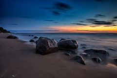 Paysage marin de coucher du soleil de mer avec les roches humides Images libres de droits