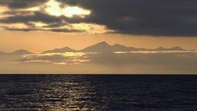 Paysage marin de stupéfaction : nuages noirs illuminés par des rayons du soleil, flottant à travers le ciel banque de vidéos