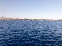 Paysage marin des belles montagnes en pierre brunes tropicales éloignées et les différentes maisons, les bâtiments sur le rivage  photo stock