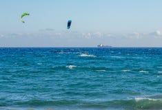 Paysage marin des surfers de cerf-volant et d'un bateau sur l'horizon Photo stock