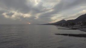 Paysage mignon de mer, ligne de côte, colline verte au coucher du soleil avec le ciel nuageux clips vidéos