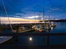 Paysage nautique des bateaux par le dock au coucher du soleil image stock