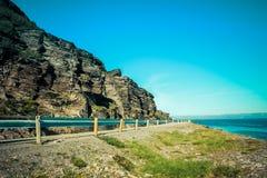 Paysage norvégien avec une route minuscule le long du bord de la mer dans un fjor images stock