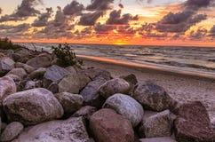 Paysage orange de coucher du soleil de mer de Baltyk avec des roches, des vagues et des nuages photo stock