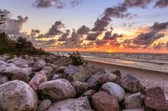 Paysage orange de coucher du soleil de mer de Baltyk avec des roches, des vagues et des nuages photographie stock