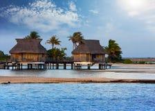 Paysage polynésien typique - petites maisons sur l'eau Photographie stock libre de droits