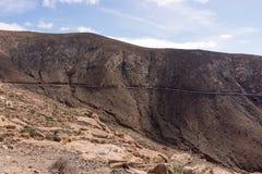 Paysage rocheux de colline avec la route à Fuerteventura photographie stock libre de droits