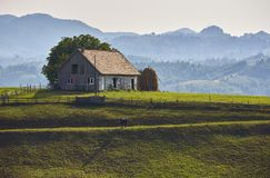 Paysage rural avec l'écurie en bois dans le passage de Rucar-son, Roumanie photographie stock libre de droits