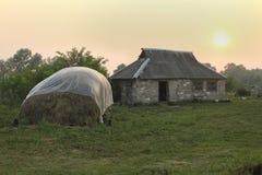 Paysage rural avec la couverture de foin contre la tente de pluie et le bui de pierre Images stock