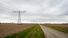 Paysage rural avec une route de campagne et des pylônes de l'électricité Image libre de droits