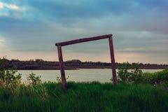 Paysage rural d'été, vue de la rivière et champ un jour nuageux, beaux nuages Construction en bois Un p antique abandonné Photographie stock