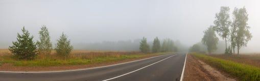 Paysage rural d'automne avec la route, le brouillard et la forêt photographie stock