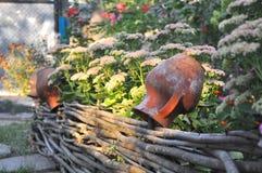 Paysage rural - vieux pots d'argile sur une barrière wattled près des fleurs photographie stock libre de droits