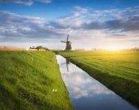 Paysage rustique avec les moulins à vent néerlandais près des canaux de l'eau Photos stock