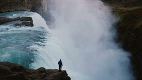 Paysage scénique de l'homme seul se tenant au bord de la montagne et regardant sur la cascade de Gullfoss en Islande Photographie stock libre de droits