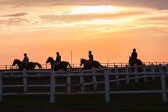 Paysage silhouetté par cavaliers de chevaux Image stock