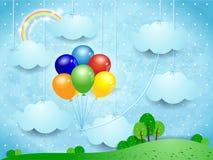 Paysage surréaliste avec les nuages et les ballons accrochants Photographie stock libre de droits