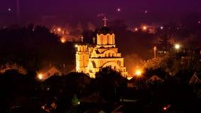 Paysage urbain de nuit avec l'église au milieu Photo stock