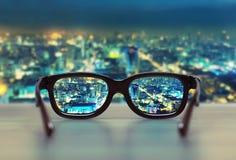 Paysage urbain de nuit focalisé dans des verres en verre Photographie stock libre de droits