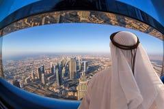 Paysage urbain de observation d'homme Arabe de Dubaï avec l'architecture futuriste moderne aux Emirats Arabes Unis Image libre de droits