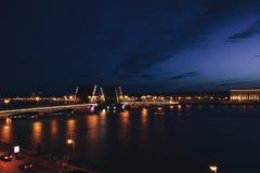 Paysage urbain de pont célèbre de palais du ` s de St Petersburg à travers Neva River la nuit Photos stock
