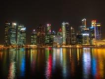 Paysage urbain de Singapour avec la réflexion la nuit Photos libres de droits