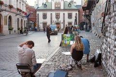 Paysage urbain de soirée - artistes qui peignent sur les rues dans la vieille ville de Cracovie Photos stock