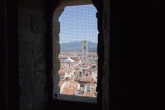 Paysage urbain florentin avec le campanile rouge de toits et de ` s de Giotto Vue d'une fenêtre étroite avec la grille de fer de  Photographie stock