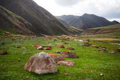 Paysage vert de vallée de montagnes Grandes pierres dans le premier plan Dessus de montagne à l'arrière-plan Images stock
