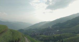 Paysan allant le long des gisements en terrasse de riz de Longji banque de vidéos