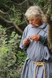 Paysan médiéval taillant un morceau au couteau de bois Photos libres de droits