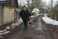 Paysan plus âgé heureux et souriant marchant sur une rue vide de village rural image stock