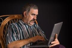 Paysan ukrainien mûr s'asseyant dans la chaise en osier et dactylographiant sur un PC d'ordinateur portable photo libre de droits