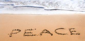 Paz escrita na areia na praia Fotografia de Stock Royalty Free