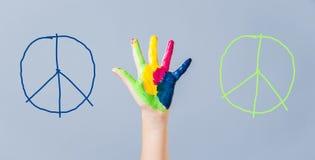 A paz pintada assina dentro a mão da menina contra a guerra Imagem de Stock Royalty Free