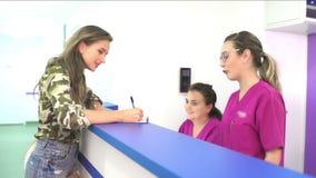 Paziente allo scrittorio di registrazione in una clinica video d archivio