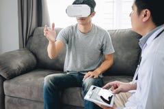 Paziente asiatico giovane dell'uomo che usando i vetri di realtà virtuale per vedere tecnologia al paziente dell'ente fisico del fotografia stock libera da diritti