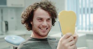 Paziente carismatico al dentista che si siede sulla sedia blu del dentista e che tiene uno specchio che esamina i suoi denti dopo video d archivio